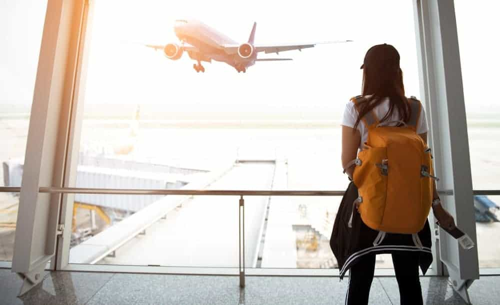 A woman with a travelling backpack waiting for her plane.