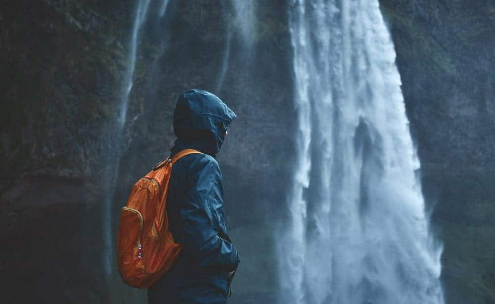 A man with a waterproof backpack by the waterfall.