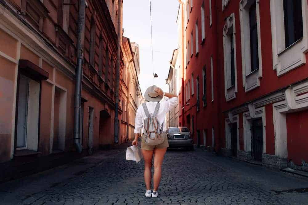 A woman in a city carrying a sightseeing daypack.