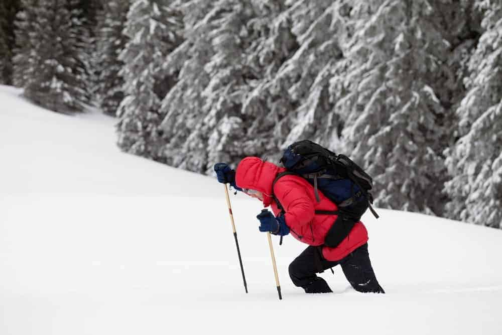 A man on a snowy mountain carrying a snowsports daypack.