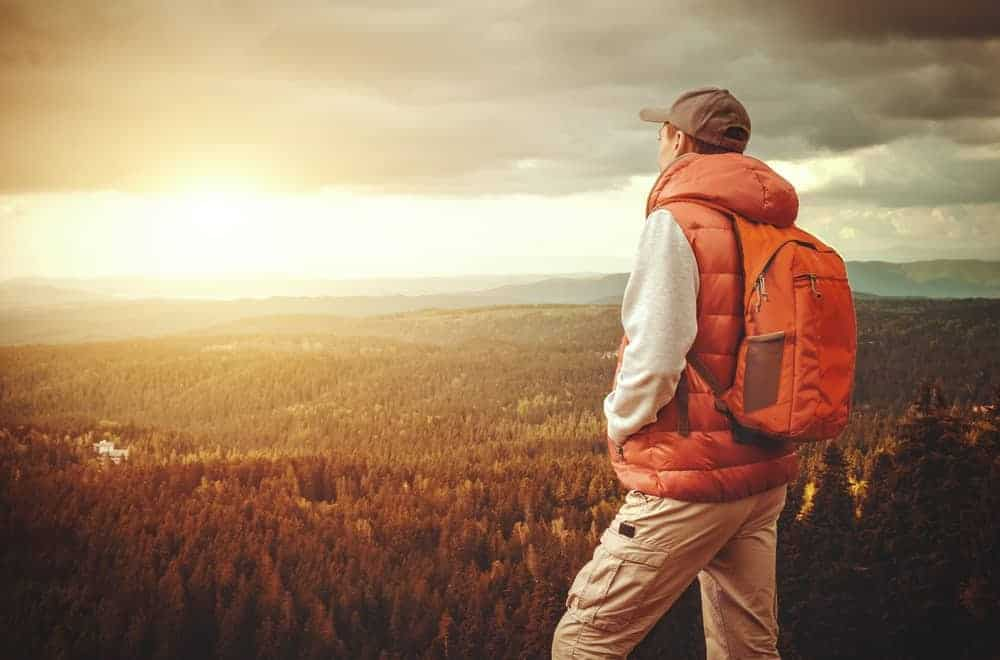 A man on a hike carrying a lightweight hiking backpack.
