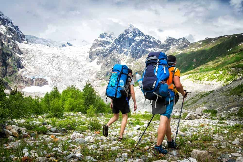 A couple of hikers carrying large trekking backpacks.