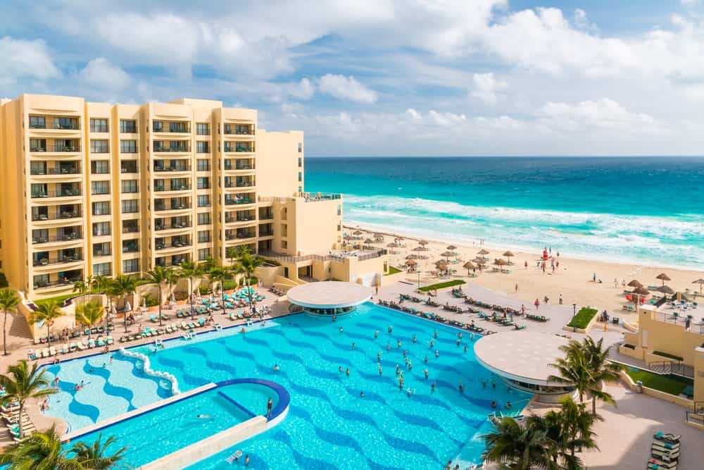 A view of a seaside resort with a large pool and a large hotel.
