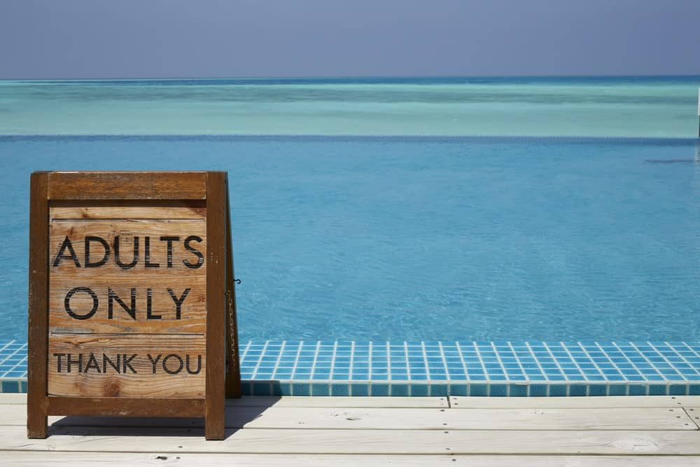 A close look at an adults-only pool with a wooden warning sign on the side.