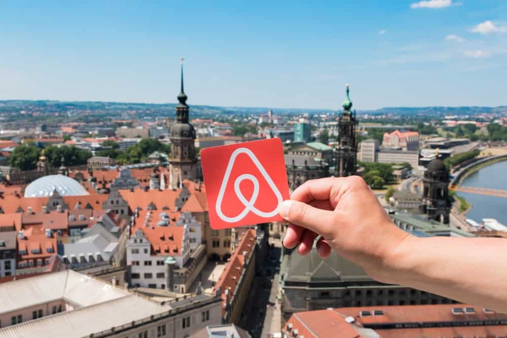 A hand holding the Aribnb logo over the sweeping view of Dresden, Germany.