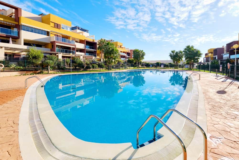 A large pool surrounded by modern luxury apartments for rent.