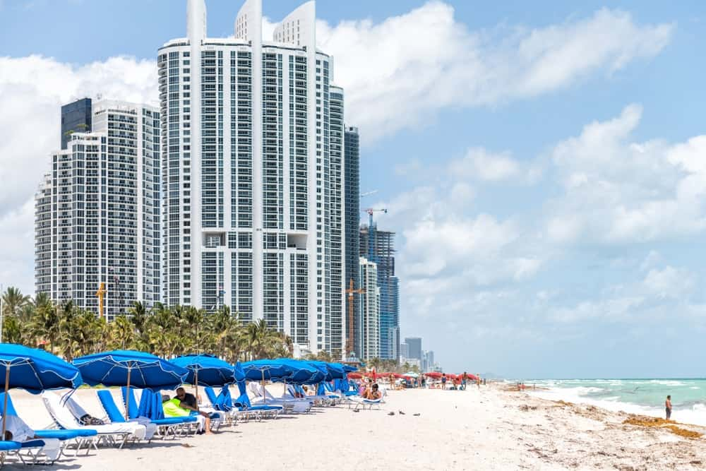 Beachers enjoying the Sunny Isles Beach with a backdrop of the Acqualina Mansions apartment buildings.