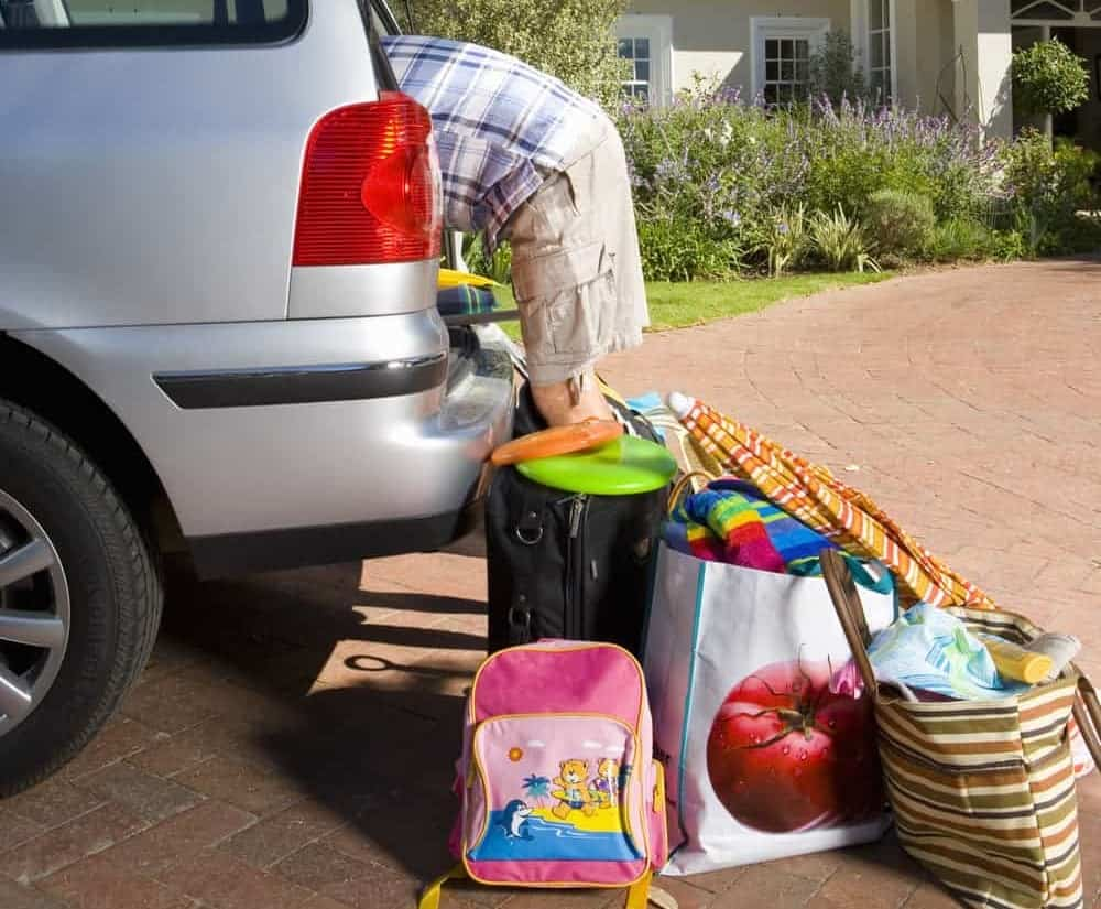 A father loading up the car for the beach trip with the kids.
