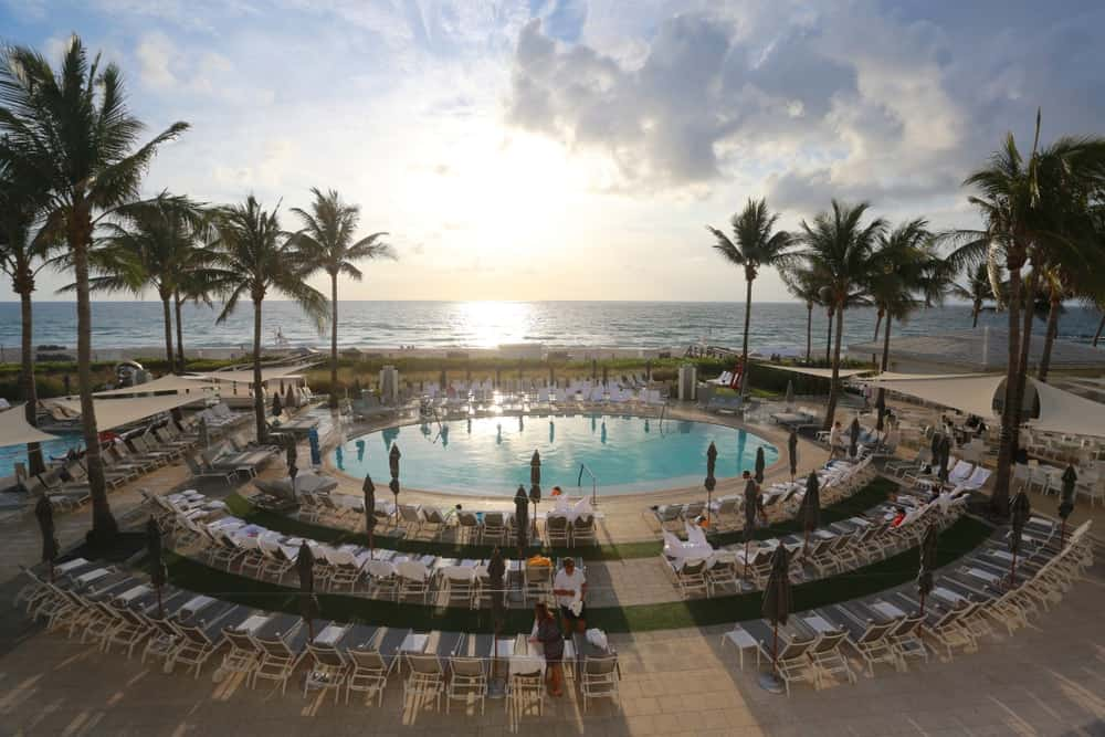 Bathers and loungers enjoy at the pool deck of Boca Beach Club flanked by palm trees and overlooking the Atlantic Ocean