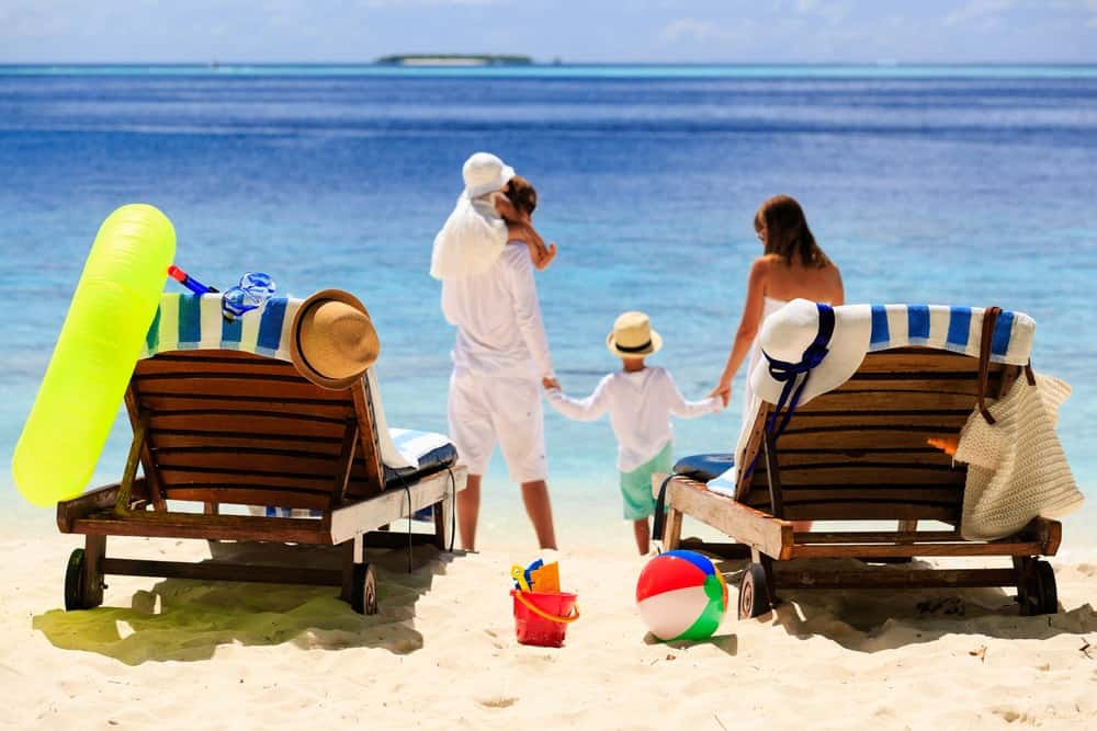 Back view of a family of four vacationing on a beach.