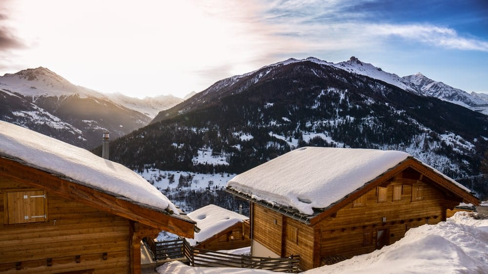 A couple of wooden holiday cottages in the alps with a sweeping view of the mountains.