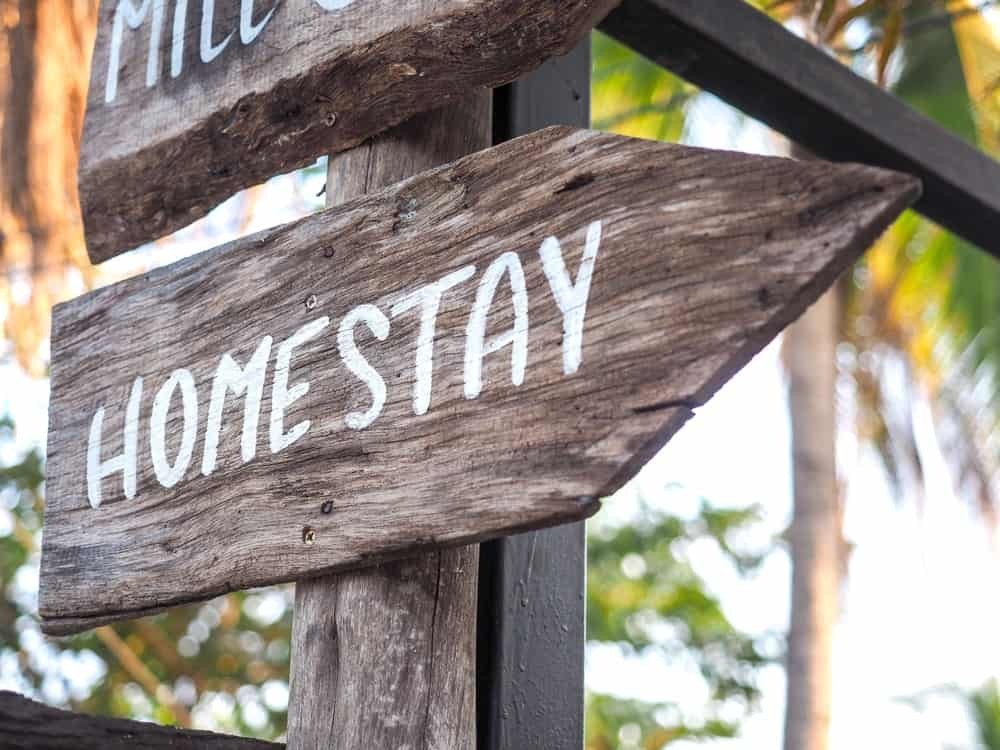 A close look at a wooden directional signage for homestay.