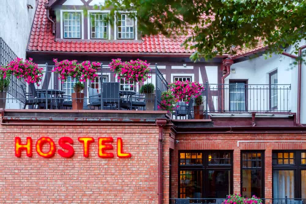An exterior look at a hostel with red brick exterior walls adorned by flowers.