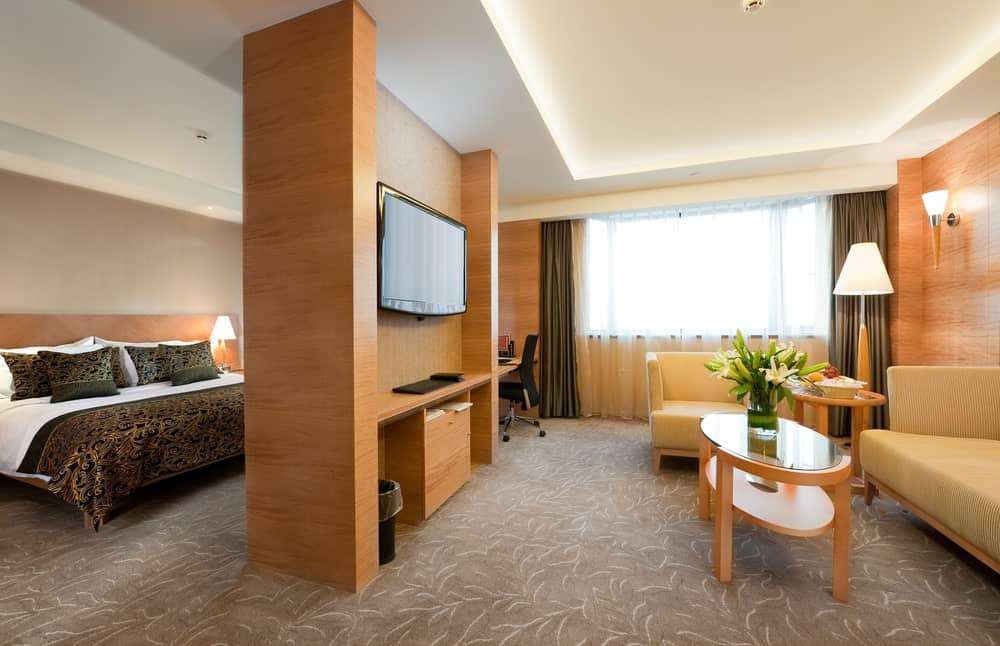This is a look at a deluxe suite hotel interior with a living room area and bedroom area divided by a wall.
