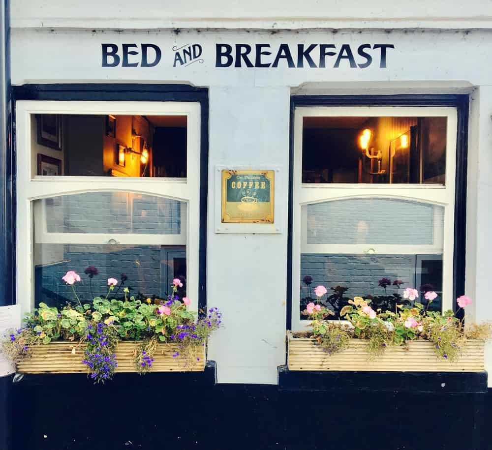A look at the homey exterior of a bed breakfast with windows adorned by planters.