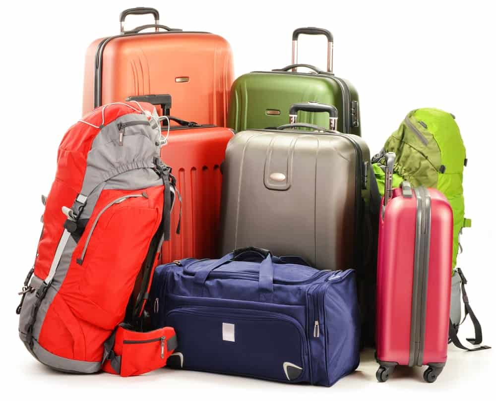 A bunch of various luggage in different colors.