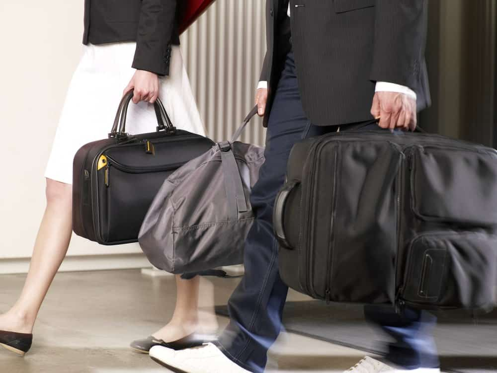 A close look at a couple walking with carry-on luggage.