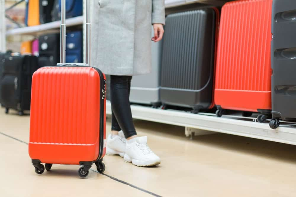 A close look at a woman shopping for a roller spinner luggage.