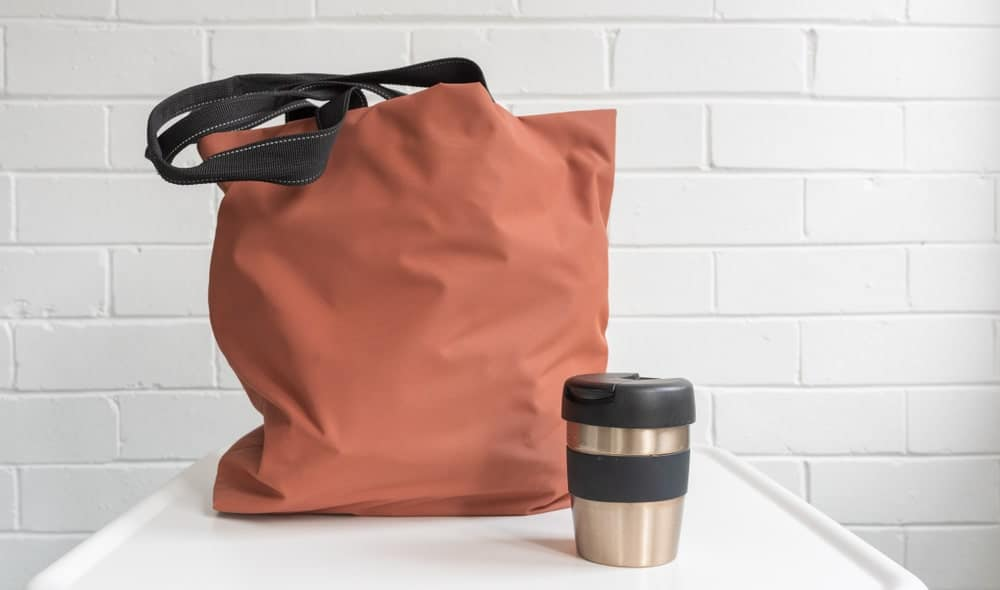 A brown travel tote bag with a tumbler.