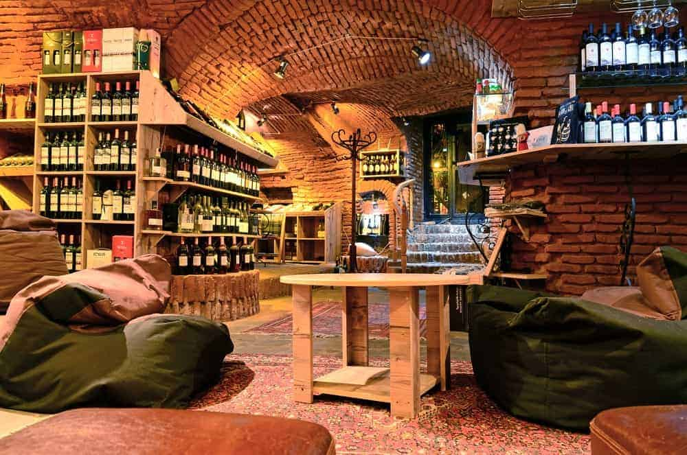 Underground bar covered in bricks from floor to ceiling, with barrel ceiling, a display of wines, bean bags, and a wooden table.