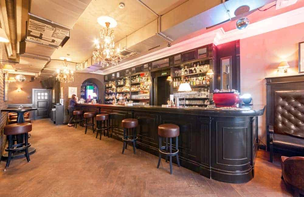 Vintage bar with chandeliers, leather bar stools, and wood flooring.