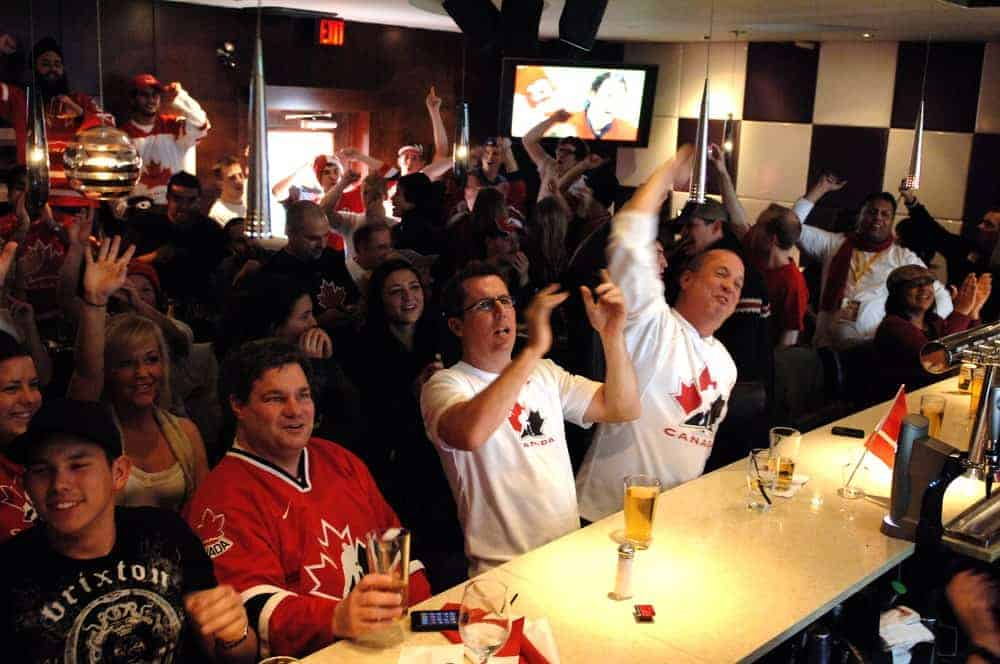 Customers react as they watch a sports game at a sports bar.