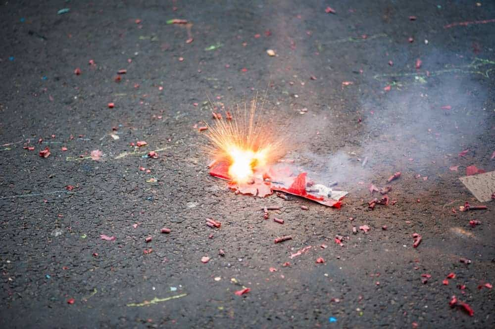 A close look at firecrackers exploding on the asphalt ground.