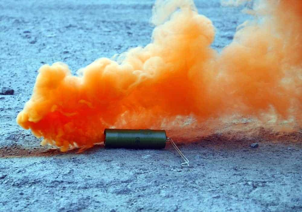 A close look at an orange smoke bomb exploding on the ground.
