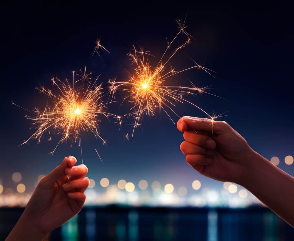 Two hands holding a sparkler firework each.