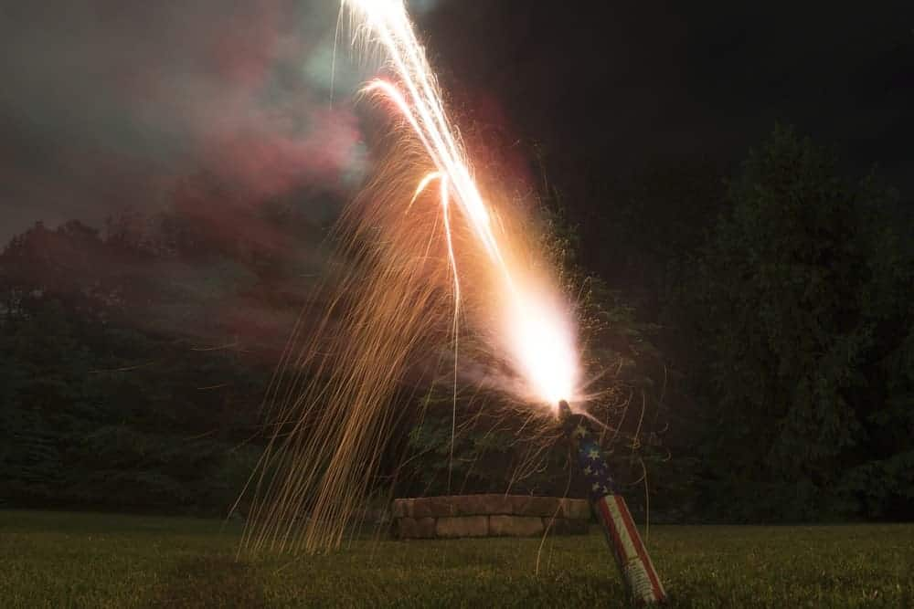A roman candle with American flag patterns on it shooting off sparks.