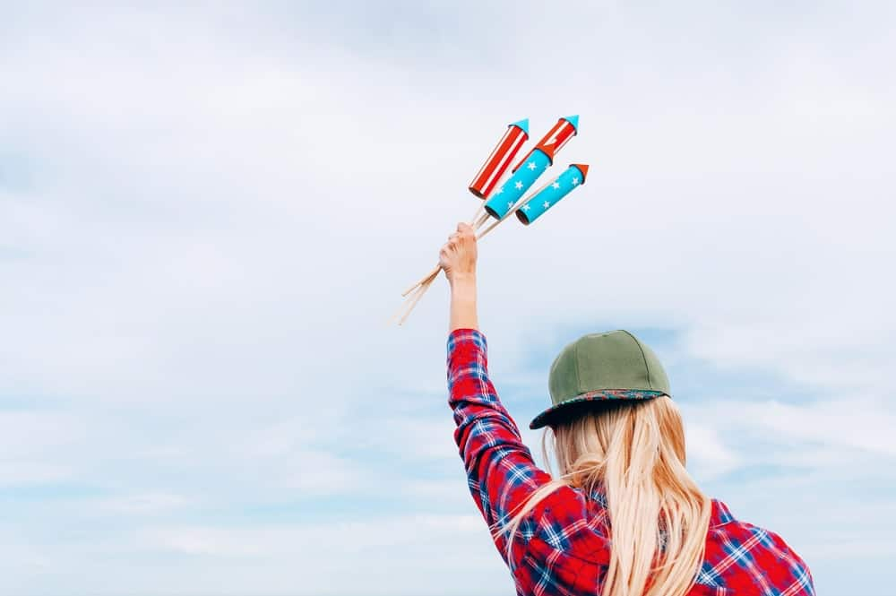 A woman holding four unlit missile fireworks up in the air.