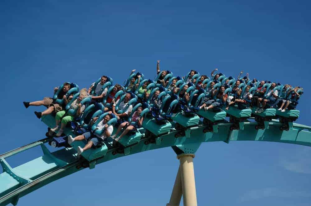 Amusement park visitors riding a floorless roller coaster.