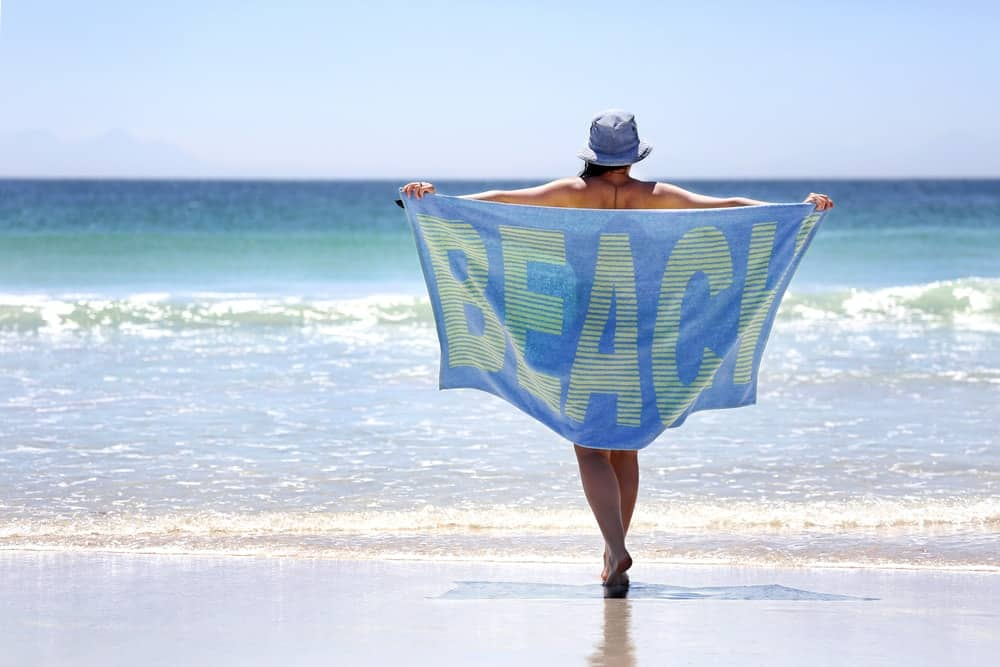 A woman walking on the beach with her beach towel.