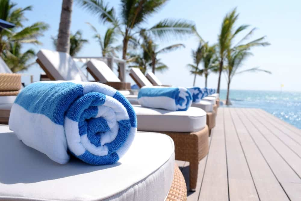 A row of rolled up quick-dry microfiber beach towels by the pool.