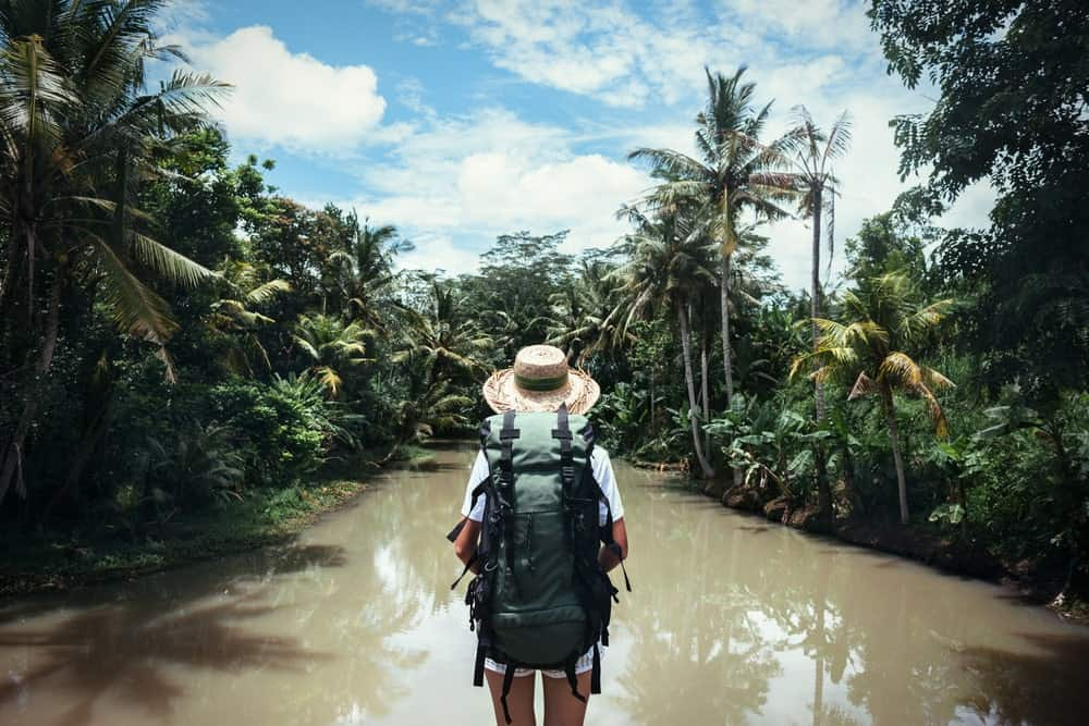 A traveling woman with a backpack and straw hat facing a river.