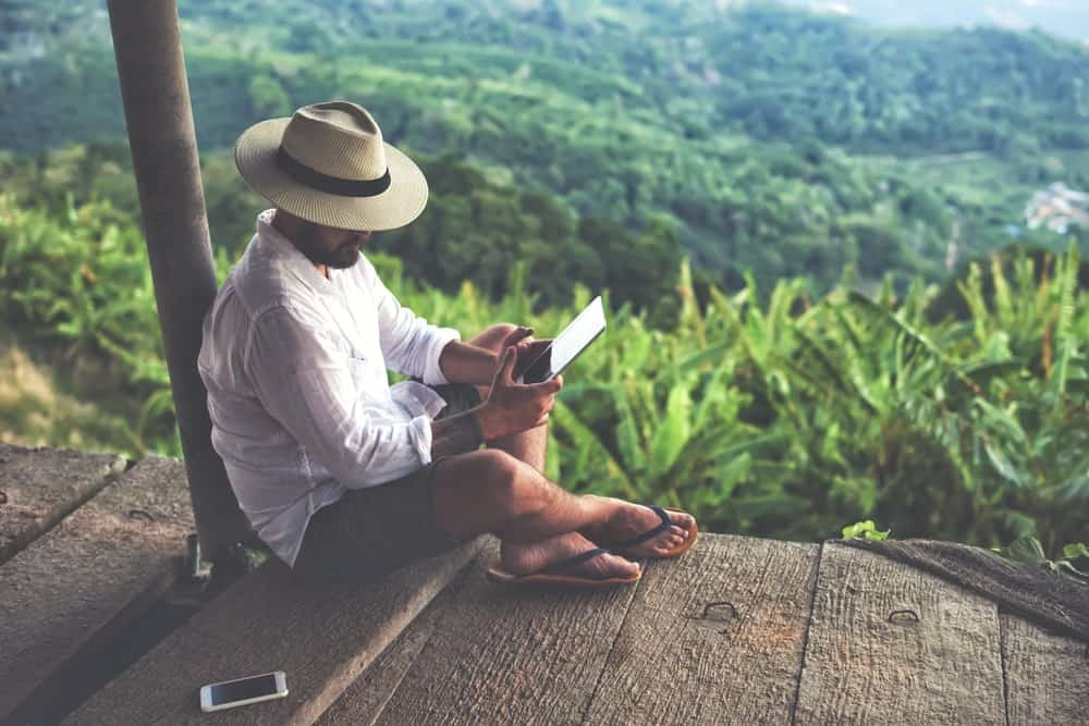 A man reading on his tablet while seating at a hut with a sweeping view of the valley.