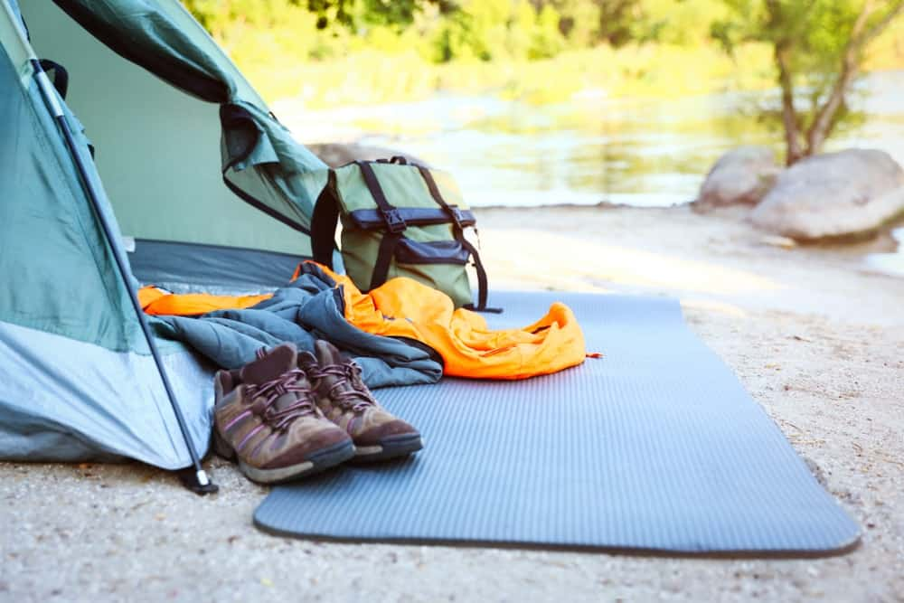 A setup of camping gear by the lake.