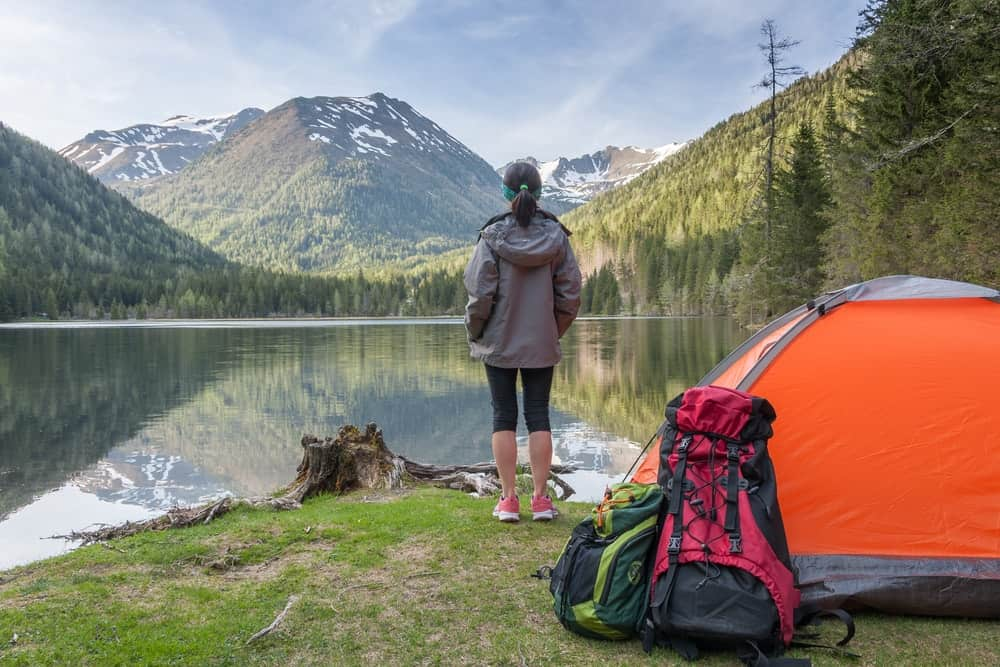 A woman on a camping trip with a tent by the lake.
