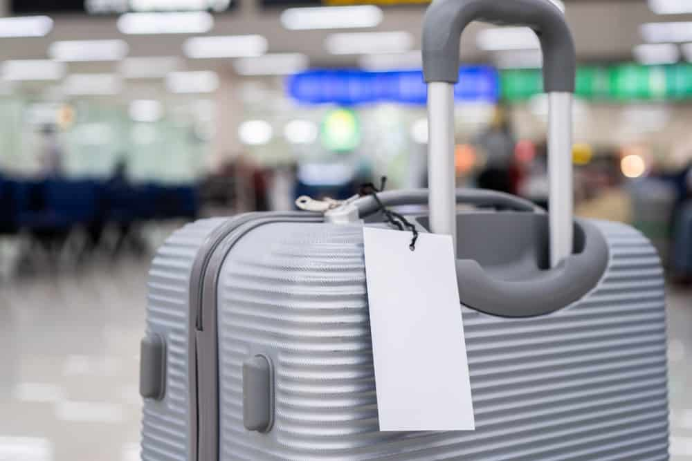 This is a close look at a gray luggage with a name card attached to it.