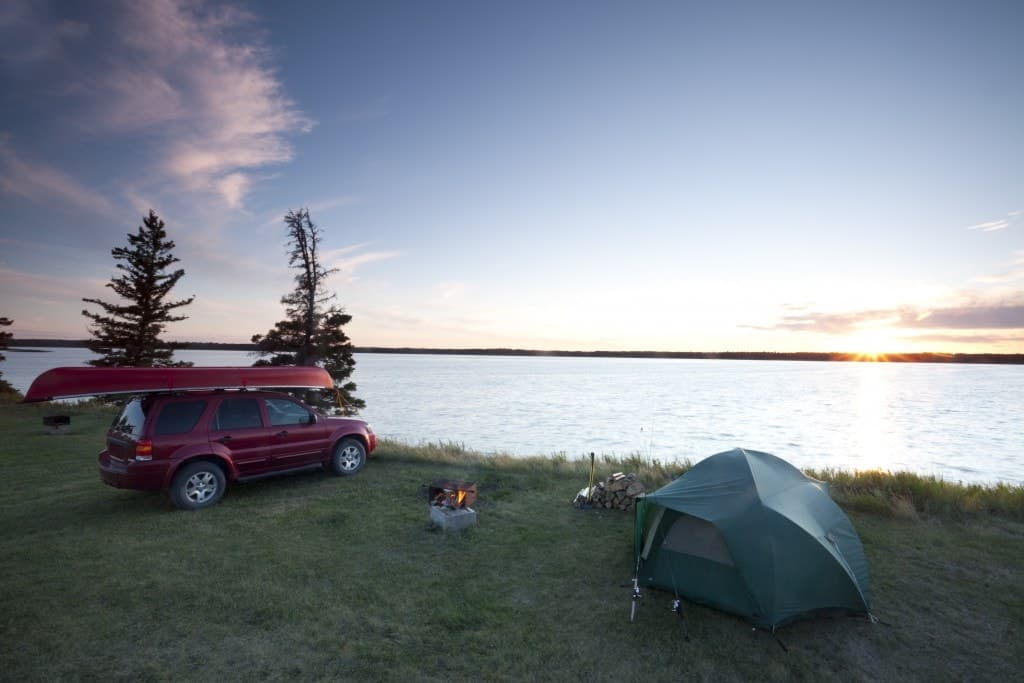 A camping spot along the water with a tent and canoe over the car.