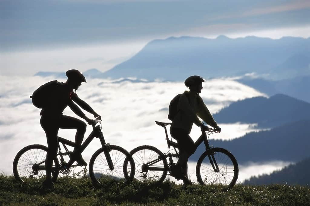 A couple of mountain bikers taking a break on a ridge looking down into a mountainous valley.