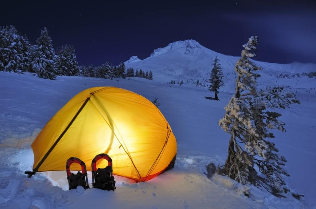 A tent set up on the snow at the base of a mountain with a light on inside.