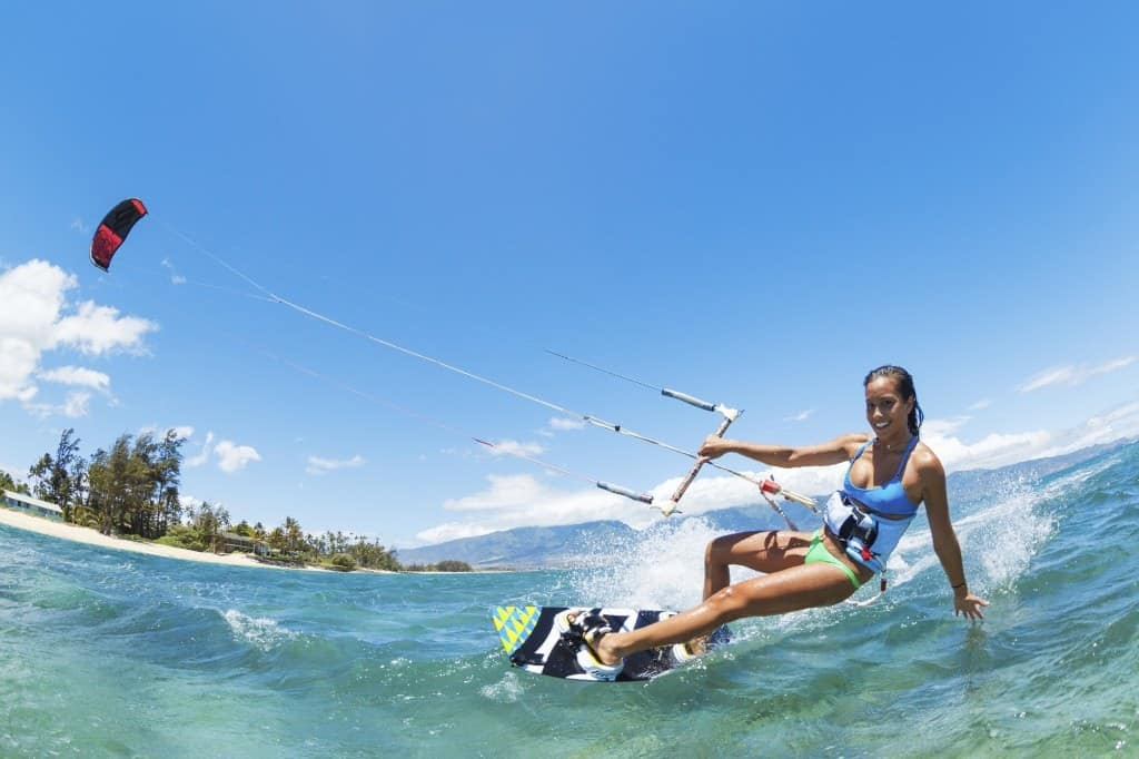 A woman Kiteboarder skimming the water on a kiteboard.