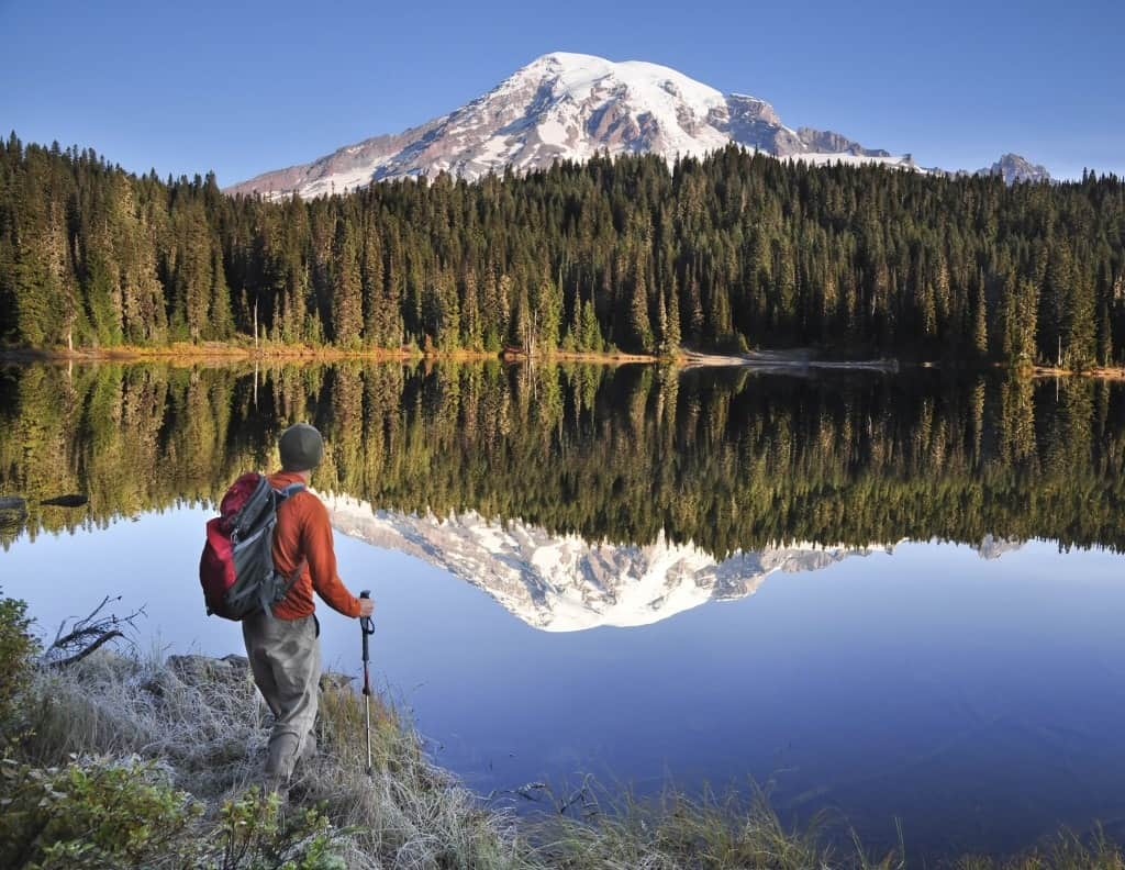 A backpacker looking at Mt Rainier and its reflection on a lake.