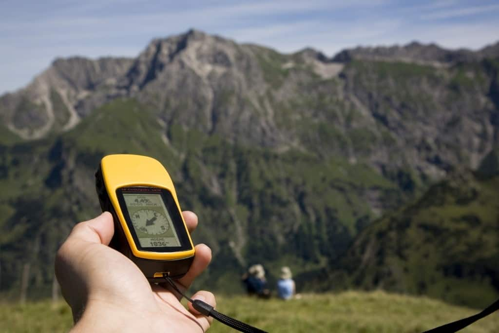 A person holding a GPS unit in the mountains.