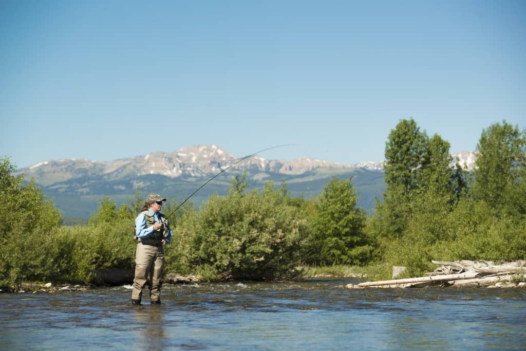 A woman fly fishing in a river.