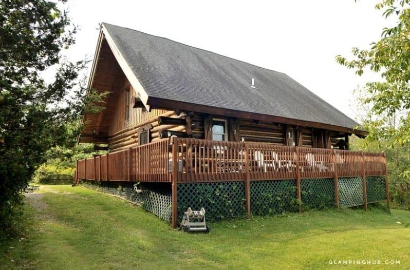 A large wooden log cabin near Lake Michigan.