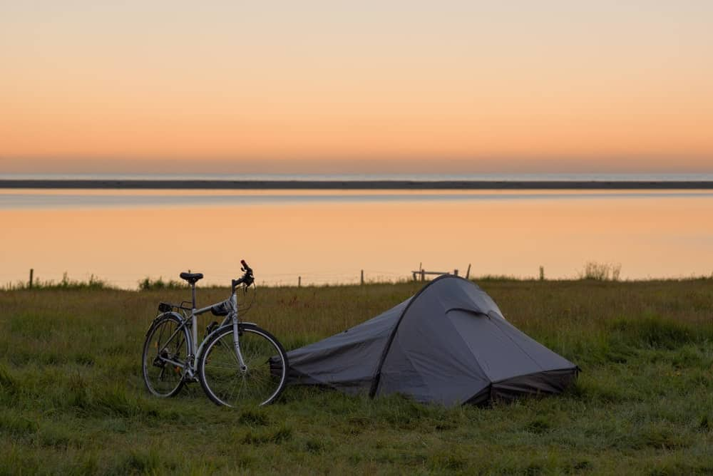 A bicycle next to camping tent.