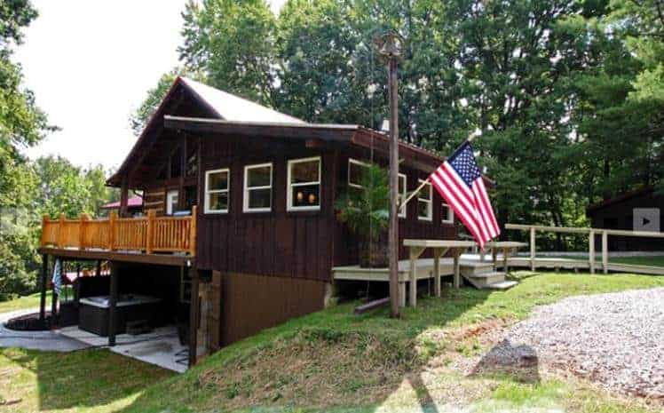 A dark brown cabin in Hocking Hills with a hot tub.