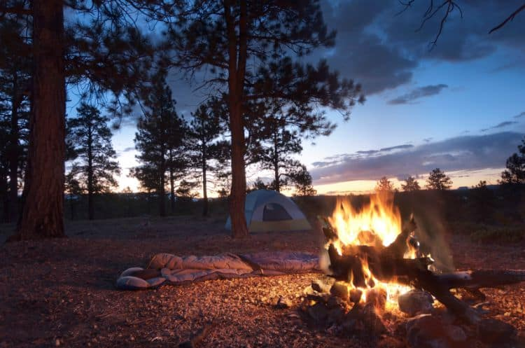 A camp set up with tent, sleeping bag and camp fire.